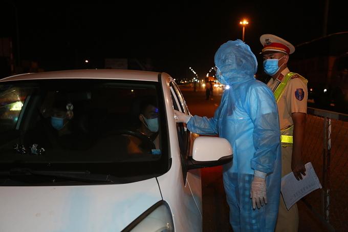 Nhân viên y tế đo nhiệt độ cho tài xế, hành khách đến TP HCM tại chốt kiểm soát dịch dưới chân cầu Đồng Nai. Ảnh: Hữu Khoa.