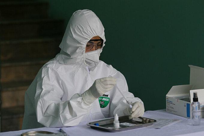 Nhana viên y tế lấy mẫu xét nghiệm. Ảnh: Tất Định