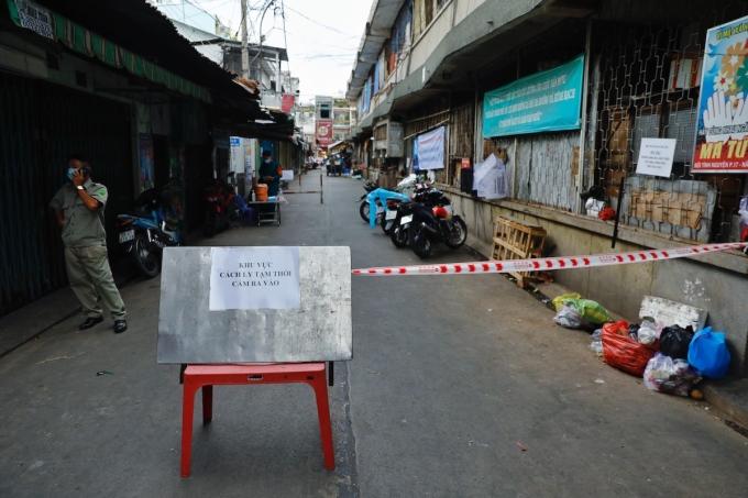Một đoạn đường trong chợ Phú Nhuận, TP HCM được khoanh vùng sáng 21/5, lực lượng y tế đang lấy mẫu khẩn cấp người có mặt trong chợ. Ảnh: Hữu Khoa