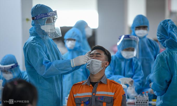 Nhân viên y tế lấy mẫu xét nghiệm cho công nhân ở Bắc Giang. Ảnh: Giang Huy