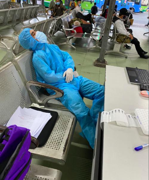 Một nhân viên y tế tranh thủ ngủ ngay tại hàng ghế chờ tại bến xe miền Đông cũ, TP HCM trong 15 phút chờ xe chuyển mẫu tới. Ảnh: Đoàn Văn Công.