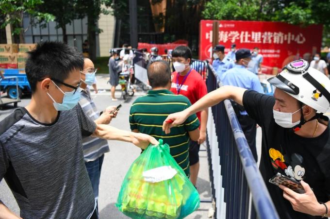 Người dân tại huyện Lệ Loan, thành phố Quảng Châu được tiếp tế nhu yếu phẩm trong thời kỳ phong toả, tháng 5/2021. Ảnh: Xinhua