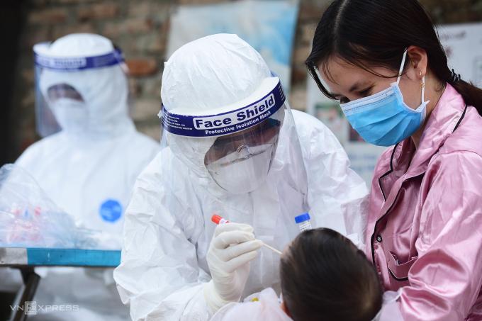 Nhận viên y tế Hà Nộ lấy mẫu xét nghiệm cho người dân tại Mê Linh, ngày 14/4. Ảnh: Giang Huy.