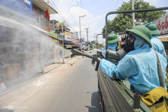Lực lượng Quân khu 7 phun hóa chất khử trùng, tiêu độc các khu vực ở phường Thạnh Lộc, quận 12, nơi có ca nhiễm covid-19, ngày 3/6. Ảnh: Quỳnh Trần.