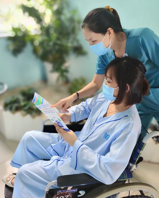 Nhân viên y tế thay người nhà chăm sóc bệnh nhân. Ảnh: Bệnh viện cung cấp