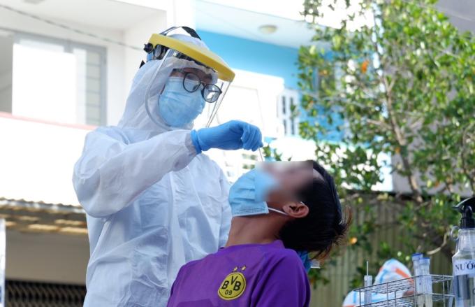 Nhân viên y tế lấy mẫu dịch hầu họng cho người dân một khu dân cư trên đường Hồ Học Lãm. Ảnh: HCDC.