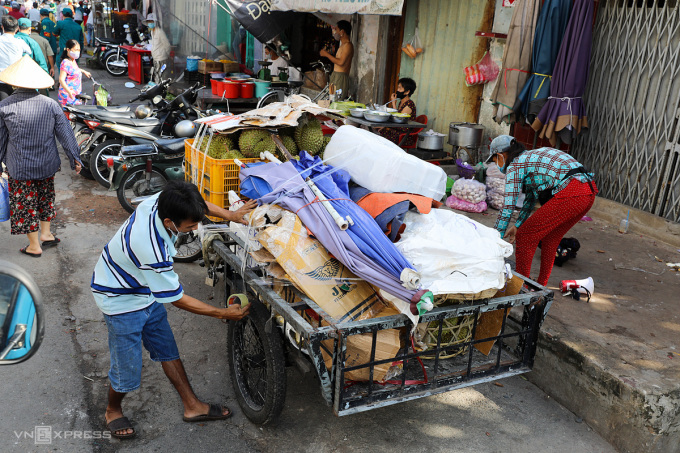 Tiểu thương chợ tự phát ở TP Thủ Đức dọn hàng khi được yêu cầu phải giải tán chợ tự phát để phòng dịch, ngày 20/6. Ảnh: Quỳnh Trần.