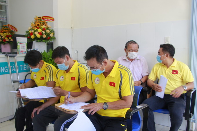 Các vận động viên điền thông tin để khám sàng lọc trước khi tiêm chủng. Ảnh: Minh Tuấn