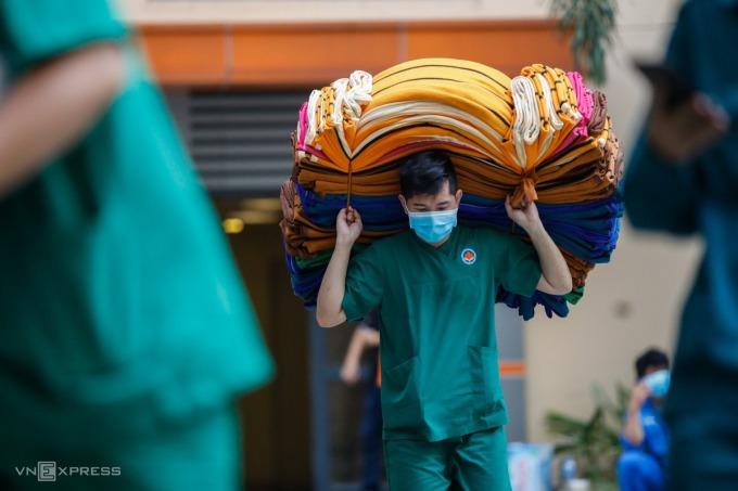 Nhân viên y tế vận chuyển mền, gối vào bệnh viện dã chiến tại TP HCM, ngày 11/7. Ảnh: Hữu Khoa.