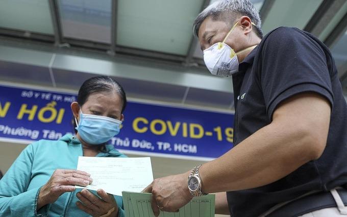 Thứ trưởng Y tế Nguyễn Trường Sơn đến thăm hỏi, trao giấy xuất viện cho bà Loan, chiều 26/7. Ảnh do bệnh viện cung cấp.