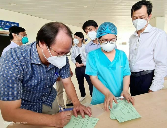 ác sĩ Lê Anh Tuấn (Phó giám đốc Bệnh viện Ung bướu TP HCM, kiêm Phó giám đốc Bệnh viện Hồi sức Covid-19) ký giấy ra viện cho bệnh nhân. Ảnh: Lê Phương.