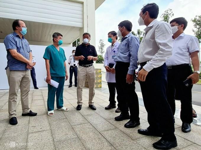 Thứ trưởng Y tế Nguyễn Trường Sơn (áo đen, ở giữa) đến thăm, động viên y bác sĩ Bệnh viện Hồi sức Covid-19, nhân dịp17 bệnh nhân đầu tiên xuất viện. Ảnh: Lê Phương.