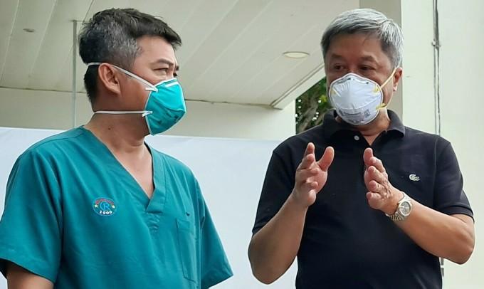 Thứ trưởng Y tế Nguyễn Trường Sơn (bên trái) trao đổi cùng bác sĩ Nguyễn Thành Linh, Phó giám đốc Bệnh viện Hồi sức Covid-19, chiều 26/7. Ảnh: Lê Phương.