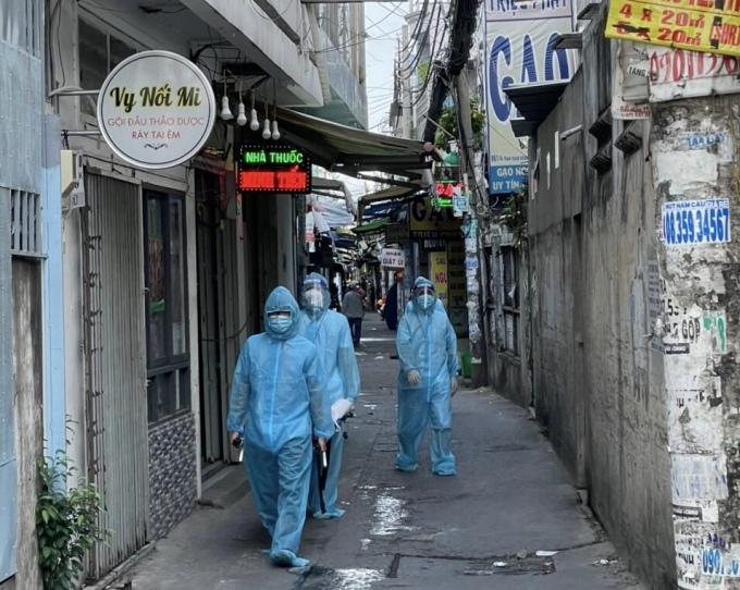 Các thành viên của tổ y tế cộng đồng phường Tân Hưng đưa người bệnh ra khỏi hẻm để lên xe cấp cứu. Ảnh: Nhân vật cung cấp