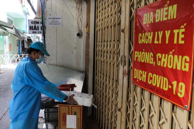 Tình nguyện viên tiếp tế nhu yếu phẩm cho từng nhà trong khu phong toả trên đường Vườn Chuối (quận 3), ngày 30/7/2021. Ảnh: Quỳnh Trần/VnExpress