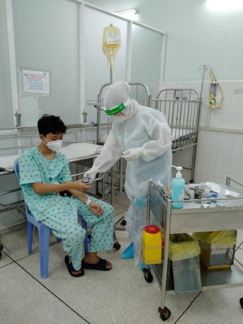 Nhân viên y tế đo SpO2 hàng ngày cho bệnh nhi Covid-19 điều trị tại bệnh viện. Ảnh: Bệnh viện Nhi đồng 2