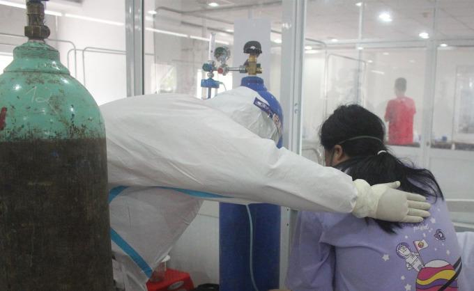 Tình nguyện viên F0 khỏi bệnh Trần Minh Khôi chăm sóc bệnh nhân trong phòng cấp cứu Bệnh viện Dã chiến 3. Ảnh: Hà Văn Đạo.