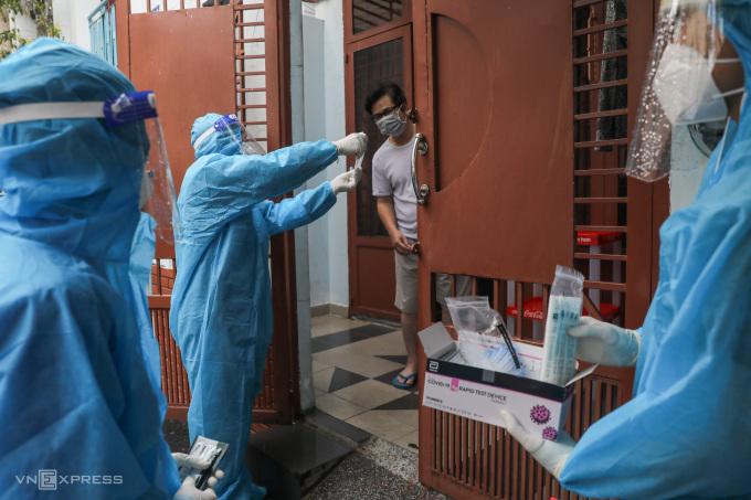 Nhân viên y tế hướng dẫn test nhanh cho người dân tại vùng đỏ ở quận Bình Thạnh, ngày 23/8. Ảnh: Quỳnh Trần.