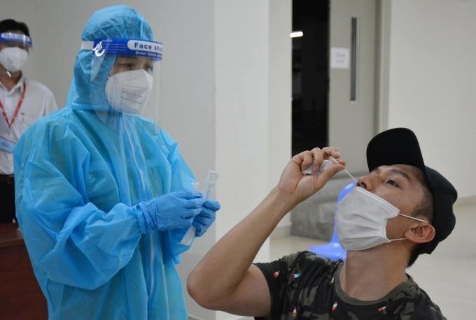 Nhân viên y tế hướng dẫn người dân tại TP Thủ Đức tự lấy mẫu xét nghiệm, tháng 7/2021.. Ảnh: Thanh Nhàn.