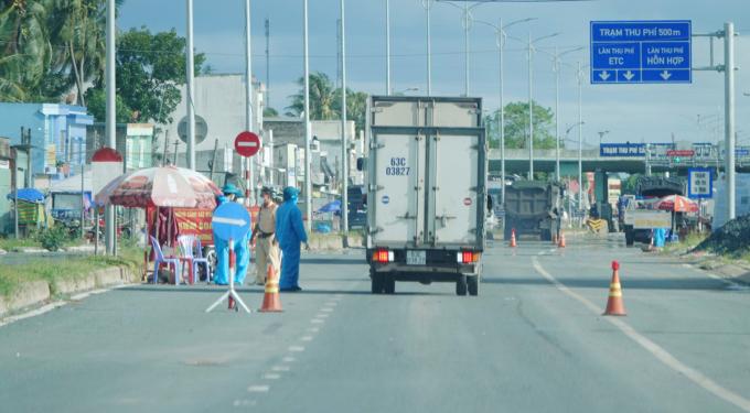 Cảnh sát kiểm tra phương tiện tại chốt đầu vào TP Bến Tre, trạm thu phí BOT cầu Rạch Miễu. Ảnh: Hoàng Nam