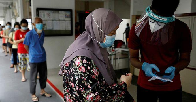 Người dân tại một khu dân cư ở Singapore xếp hàng xét nghiệm nCoV, ngày 21/5. Ảnh: Reuters